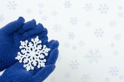 Handen die blauwe handschoenen dragen die een grote sneeuwvlok houden Royalty-vrije Stock Afbeeldingen