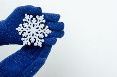 Handen die blauwe handschoenen dragen die een grote sneeuwvlok houden. Stock Afbeeldingen