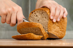 Handen die brood, close-up snijden Royalty-vrije Stock Afbeelding
