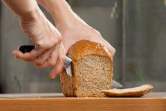 Handen die brood snijden Stock Foto