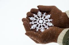 Handen die bruine handschoenen dragen die een grote sneeuwvlok houden Royalty-vrije Stock Afbeelding