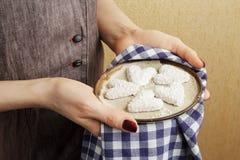 Handen die ceramische plaat met koekjes in de vorm van een hart, de Dagconcept houden van StValentine ` s Royalty-vrije Stock Afbeeldingen