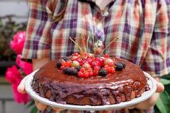 Handen die chocoladecake houden die met bessen wordt verfraaid Stock Afbeeldingen