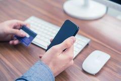 Handen die creditcard en het typen op de telefoon houden die online aankoop maken royalty-vrije stock foto