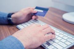 Handen die creditcard en het typen op toetsenbord houden die online aankoop maken stock afbeelding