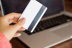Handen die creditcard houden en laptop met behulp van Online Winkelend stock foto