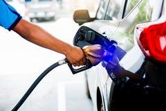 Handen die de auto met brandstof bij het benzinestation, zwarte auto in benzinestation opnieuw vullen royalty-vrije stock foto
