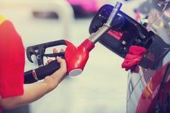 Handen die de auto met brandstof bij het benzinestation, zwarte auto in benzinestation opnieuw vullen royalty-vrije stock foto's