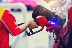 Handen die de auto met brandstof bij het benzinestation, zwarte auto in benzinestation opnieuw vullen stock foto