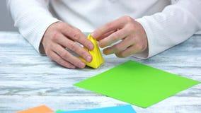 Handen die de bol van de origamitulp vouwen stock footage