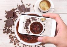 Handen die de chocoladecake van de fototruffel met smartphone nemen Stock Foto
