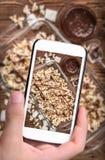 Handen die de karamelpopcorn van de foto donkere chocolade met smartphone nemen Royalty-vrije Stock Afbeelding