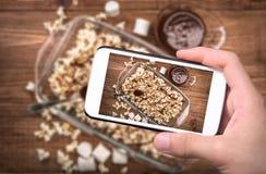 Handen die de karamelpopcorn van de foto donkere chocolade met smartphone nemen Royalty-vrije Stock Fotografie