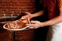 Handen die de pizza uitrekken Stock Fotografie