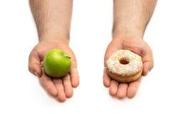 Handen die een appel en een doughnutconcept een taaie keus tussen tegenovergesteld alternatieven gezond voedsel houden versus zoe royalty-vrije stock fotografie