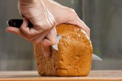 Handen die een brood van brood snijden Stock Afbeelding