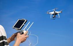 Handen die een camera houden van de afstandsbedieninghommel terwijl het vliegen in stock fotografie