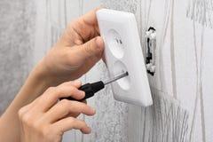 Handen die een contactdoos van de muurmacht installeren Stock Fotografie