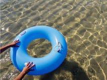 Handen die een doughnut opblaasbaar in het overzees duwen Royalty-vrije Stock Foto