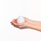 Handen die een ei op witte achtergrond houden Royalty-vrije Stock Afbeeldingen