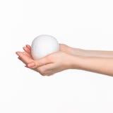 Handen die een ei op witte achtergrond houden Stock Afbeelding