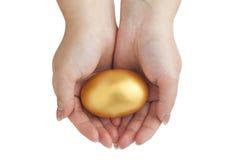 het gouden ei in handen stock afbeeldingen