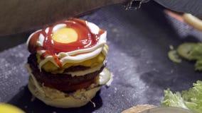 Handen die een hamburger voorbereiden Sluit omhoog mening van het voorbereiden van een rundvleeshamburger bij het festival van he stock footage