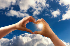 Handen die een hartvorm met blauwe hemel vormen Royalty-vrije Stock Afbeelding