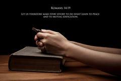 Handen die een kruis op heilige Bijbel met vers houden Royalty-vrije Stock Fotografie