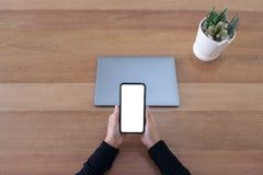 Handen die een lege witte het scherm mobiele telefoon en laptop op houten lijst in bureau houden royalty-vrije stock afbeeldingen