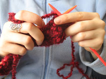 Handen die een magenta sjaal breien Stock Afbeeldingen