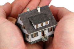Handen die een miniatuurhuis houden Stock Afbeelding