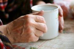 Handen die een mok met een drank houden stock fotografie