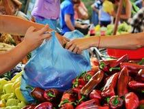 Handen die een plastic zak vullen met verse groenten Stock Afbeeldingen