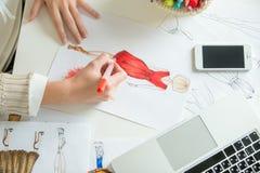 Handen die een schets van het kledingsontwerp kleuren royalty-vrije stock afbeelding