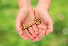 Handen die een sleutel houden stock afbeeldingen