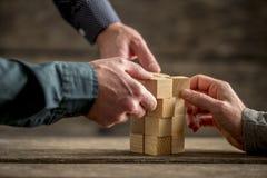 Handen die een toren van houtsneden bouwen Stock Foto