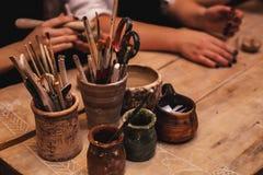 Handen die en beeldhouwwerk met klei werken beëindigen stock fotografie