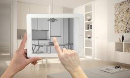 Handen die en op tablet houden richten die moderne keukencad schets tonen Echte gebeëindigde minimalistische witte keuken op de a royalty-vrije stock afbeelding