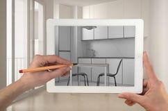 Handen die en op tablet houden trekken die moderne keukencad schets tonen Echte gebeëindigde minimalistische witte en houten keuk royalty-vrije stock afbeelding