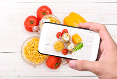 Handen die foto eigengemaakte gezonde salade in glaskruik nemen met smartphone Stock Foto's