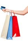 Handen die gekleurde het winkelen zakken op witte achtergrond houden Stock Foto