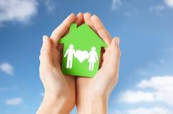 Handen die groen huis met familiepictogram houden Royalty-vrije Stock Foto