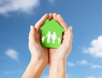 Handen die groen huis met familiepictogram houden Stock Foto's