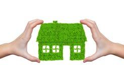 Handen die groen huissymbool houden Stock Afbeeldingen