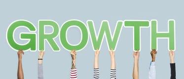 Handen die groene brieven steunen die de woordgroei vormen stock foto