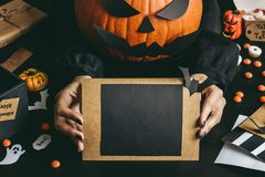 Handen die Halloween-kaart houden die van ambachtdocument wordt gemaakt De ruimte van het exemplaar Stock Afbeelding