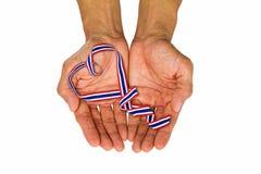 Handen die hart gevormd Thais nationaal kleurenlint op witte B houden Royalty-vrije Stock Foto's
