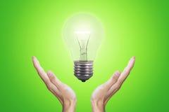 Handen die heldere lightbulb houden stock foto's