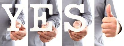 Handen die het woord van de brieventekst ja houden Stock Foto